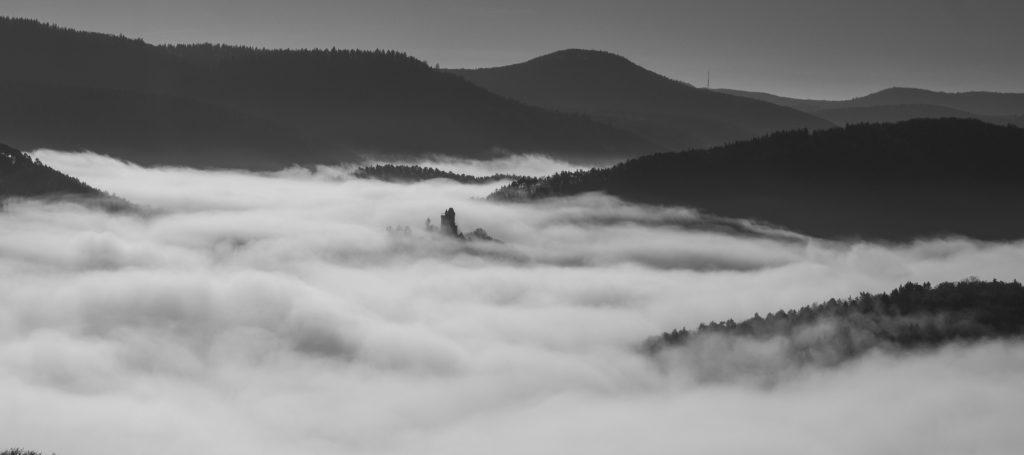 Auch eine Schwarzweißaufnahme kann ausdrucksstark sein. In der Bildmitte ragt die Burg Berwartstein aus der Nebeldecke.
